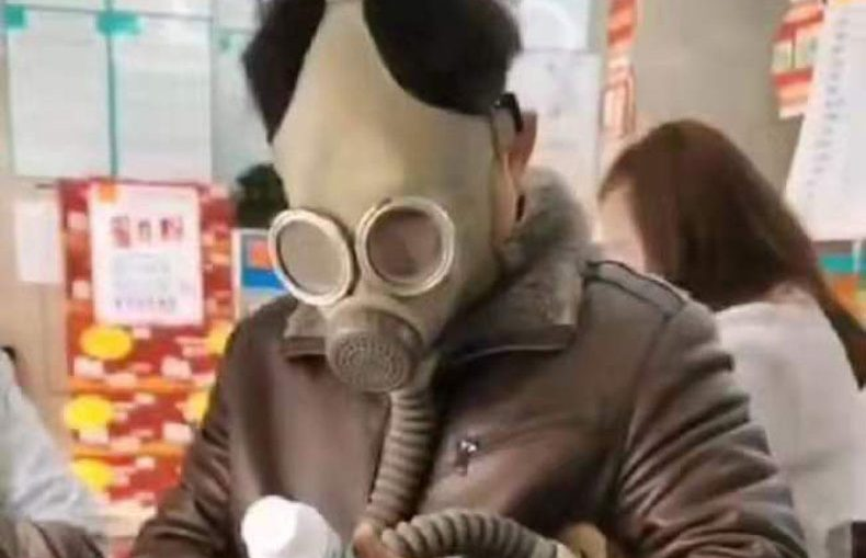 Wuhan citizen wearing a gas mask holding medicine bottle